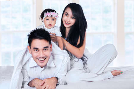 Young family with baby girl playing on the bed at home photo