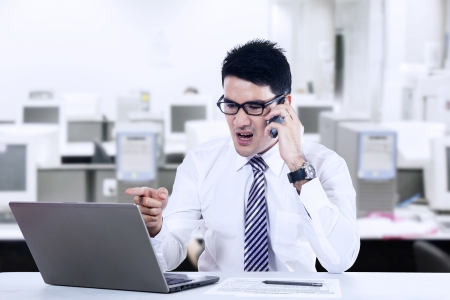 Young businessman with a phone and laptop screaming and shouting photo