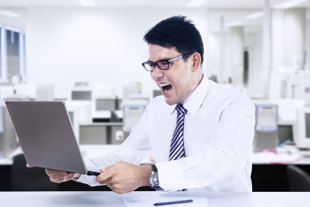Angry businessman with a laptop in office photo