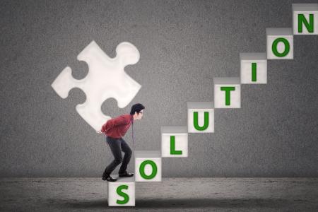 apporter: Homme d'affaires apporter solution de puzzle sur fond gris Banque d'images