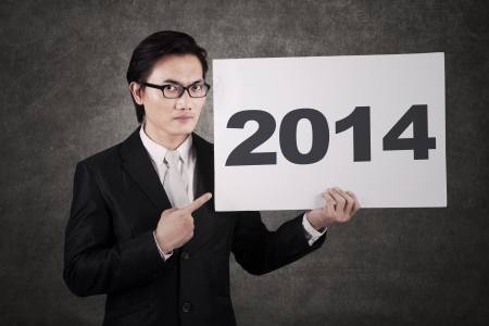 Young businessman pointing a 2014 billboard on gray  photo