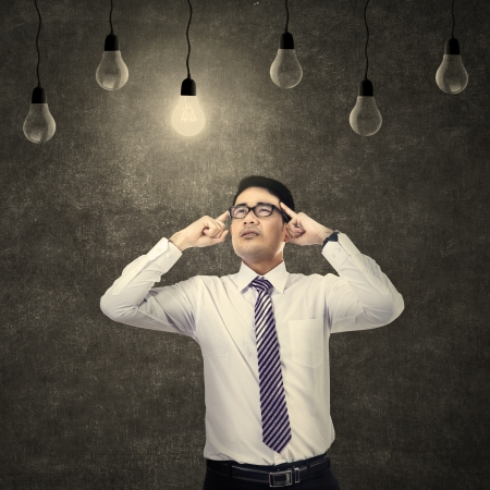 Young businessman thinking under light bulb photo