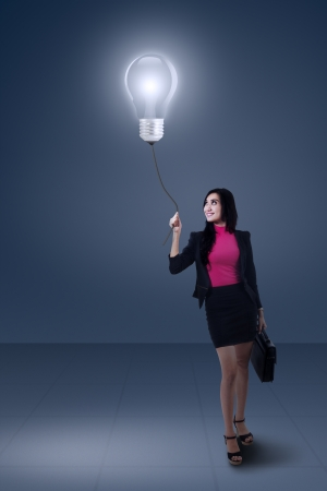 Portrait of businesswoman holding bright light bulb photo