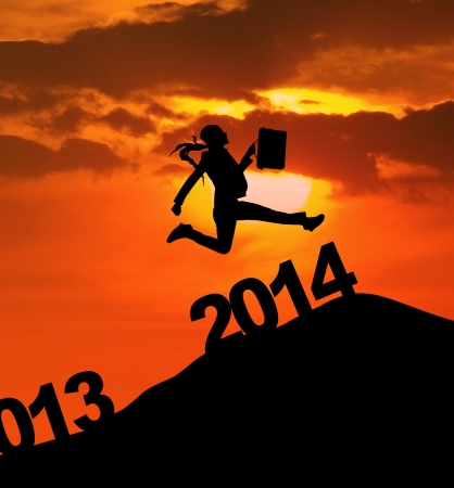 Silhouette of businesswoman is jumping over 2014 New Year photo