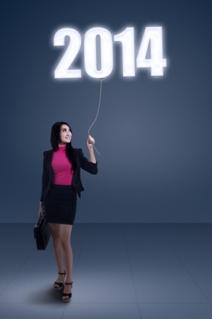 A concept of businesswoman standing under new year 2014 photo