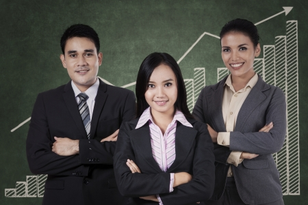 Portrait of confident businessteam with graph