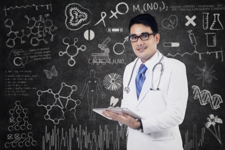 young male doctor: Young male doctor is writing a note standing on class