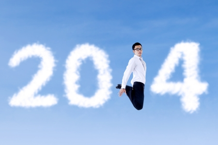 Excited asian businessman is jumping with clouds of 2014 on the blue sky Stock Photo - 23963288