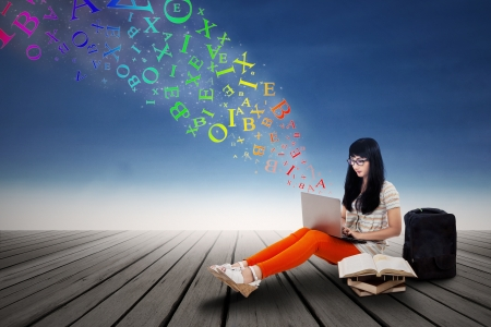 Beautiful female student typing on a laptop with flying letters outdoor photo