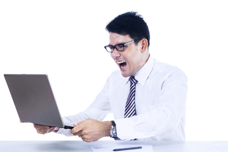 Furious businessman with laptop computer on white  photo
