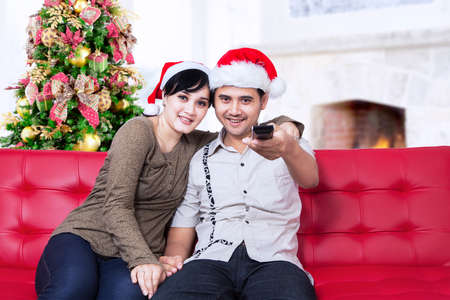 asian family home: Happy christmas couple wearing santas hats and holding a remote control Stock Photo