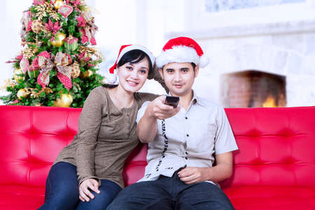 Happy christmas couple watching tv at home photo