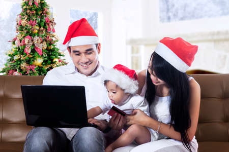 Happy christmas family using a notebook at home photo