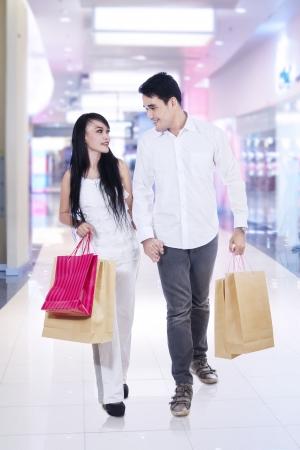 indonesian woman: Feliz pareja caminando por el centro comercial con bolsas de compras
