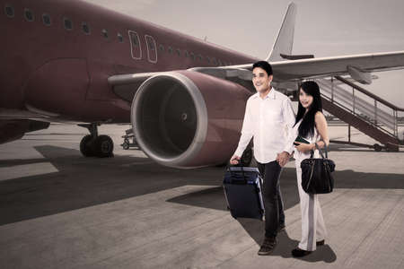 Happy loving couple traveling by airplane and smiling photo