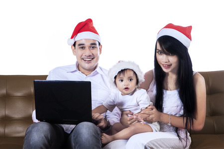 Portrait of happy family with notebook on Christmas day photo
