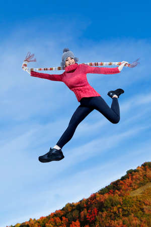 Happy asian girl jumping on the autumn park photo