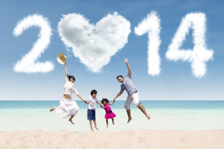 Happy family having fun in the beach with heart shaped cloud of new year 201 photo