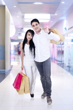 Romantic couple with shopping bags in shopping center photo