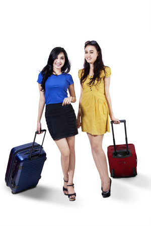 Two young woman friend traveling with suitcase, isolated on white  photo