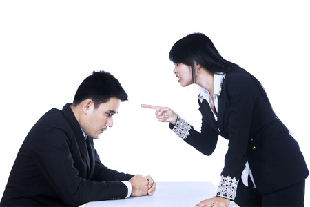 business disagreement: Upset manager pointing to her employee isolated on white  Stock Photo