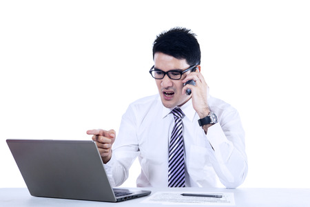 filipino adult: Young businessman is shouting by phone. Isolated on white Stock Photo