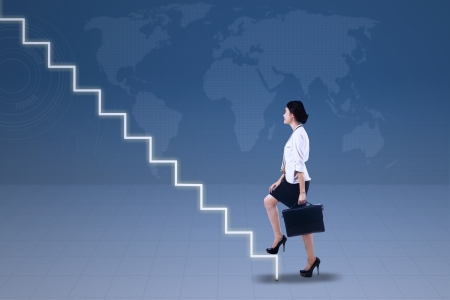 climbing stairs: Young businesswoman walking up on stairs with world map  Stock Photo