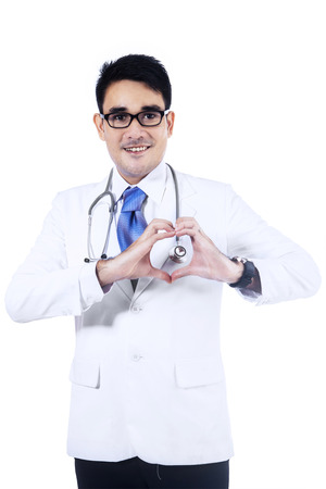 Young male doctor showing heart sign isolated on white  photo
