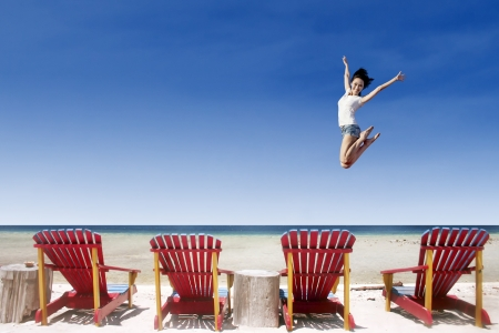 whitehaven beach: Active girl jumping over beach chairs at Whitehaven beach, Australia