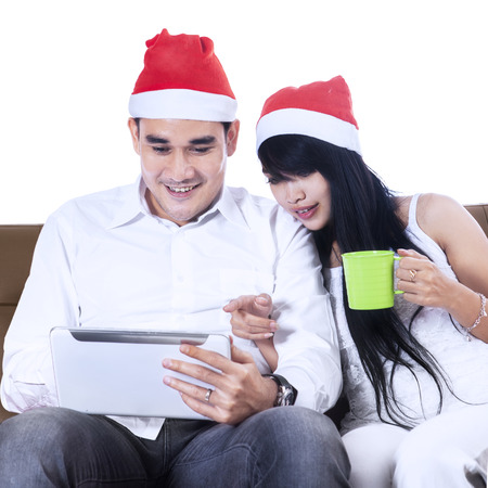 Portrait of happy christmas couple using digital tablet to shopping online. isolated on white photo
