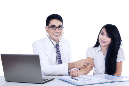 check up: Young asian doctor examines his patient -  isolated on white background Stock Photo