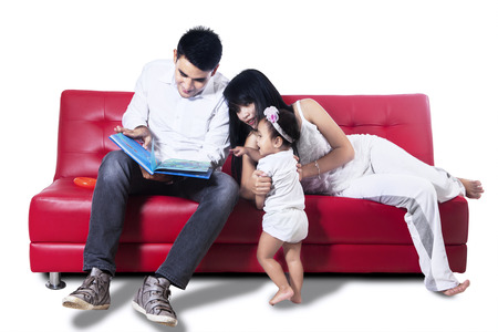 family sofa: Young parents read the book to their baby - isolated on white background
