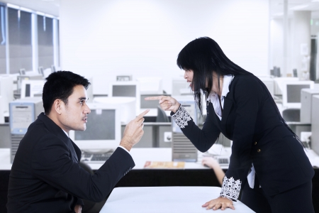 Businesspeople in an Office Fighting and Pointing Fingers at Each Other photo