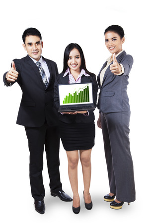 Group of business people showing growth graph on laptop and giving thumbs up photo