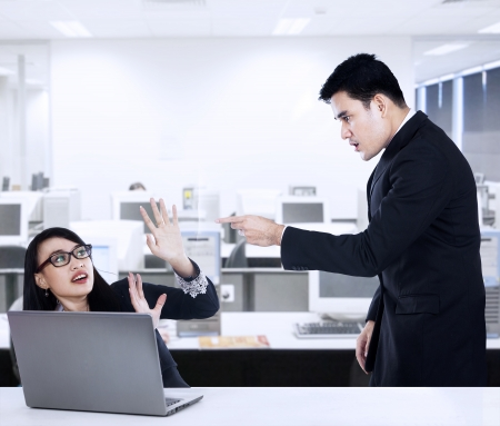 Businessman is yelling at his employee in office photo