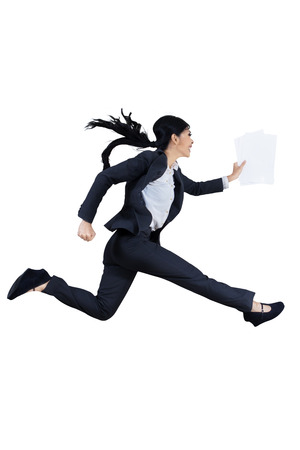The young beautiful woman runs by holding business paper photo