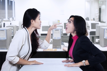 Two asian businesswomen fighting at office photo