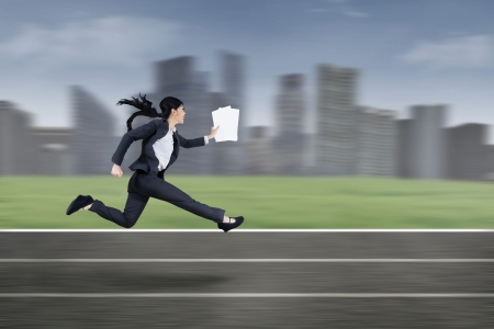 late 20s: The young beautiful businesswoman runs by holding business paper Stock Photo