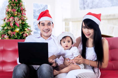 Smiling christmas family using a notebook at home photo