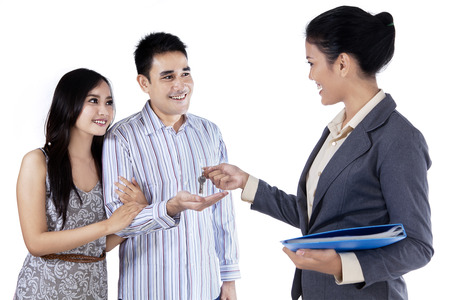 agents: Happy couple getting keys of their new home from businesswoman Stock Photo