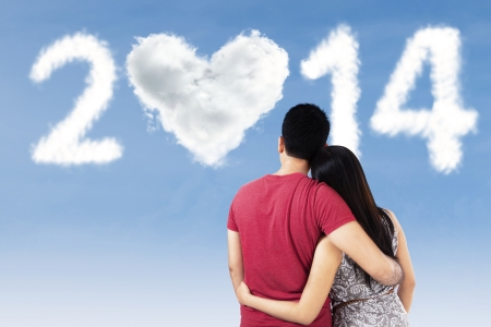 Young couple looking at clouds shape of number 2014 with love on the sky photo