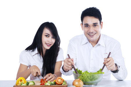 Happy couple preparing salad together. isolated on white background photo