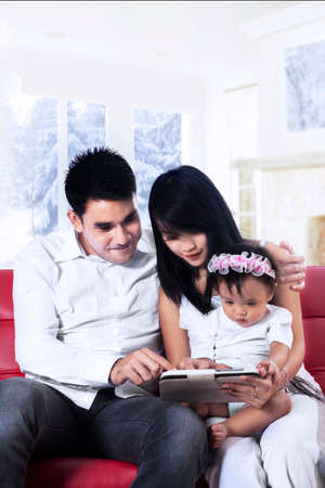 indian happy family: Happy family holding a digital tablet sitting on red couch Stock Photo