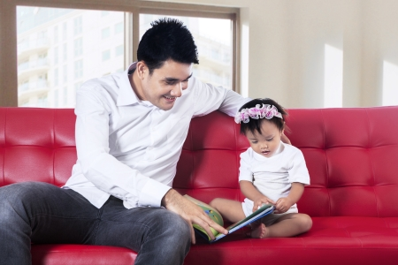 Lovely father reading story book with his baby at home photo