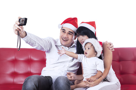 Happy christmas family take a photo sitting on red couch photo