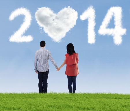 Happy couple holding hands looking in the future of new year 2014 photo