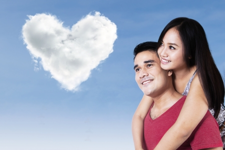 Happy couple looking at the beautiful love shape clouds under blue sky photo