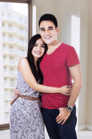 filipino adult: Happy young couple standing in their new apartment