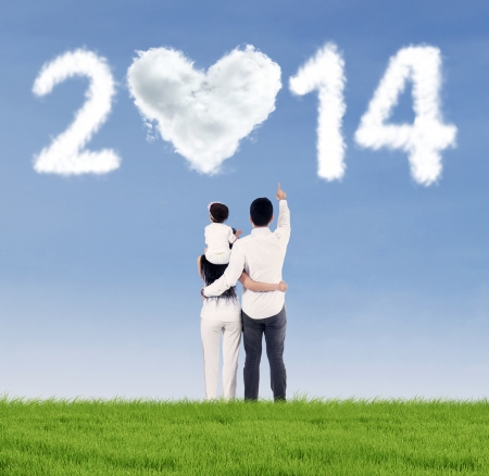 Happy family on the meadow and pointing at the heart shaped cloud of new year 2014 photo