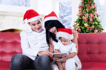 Happy family using tablet computer sitting near Christmas tree photo